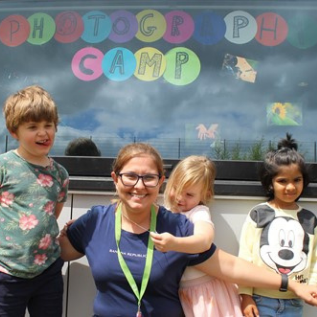 Experienced childcare professional and children enjoying summer camp.